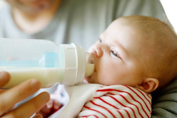 Vater Fütterung neugeborenen Tochter mit Milch in Babyflasche – Foto