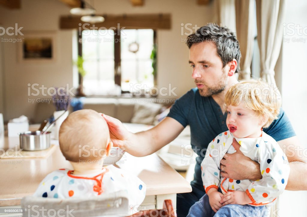 Father feeding two toddlers at home. stock photo