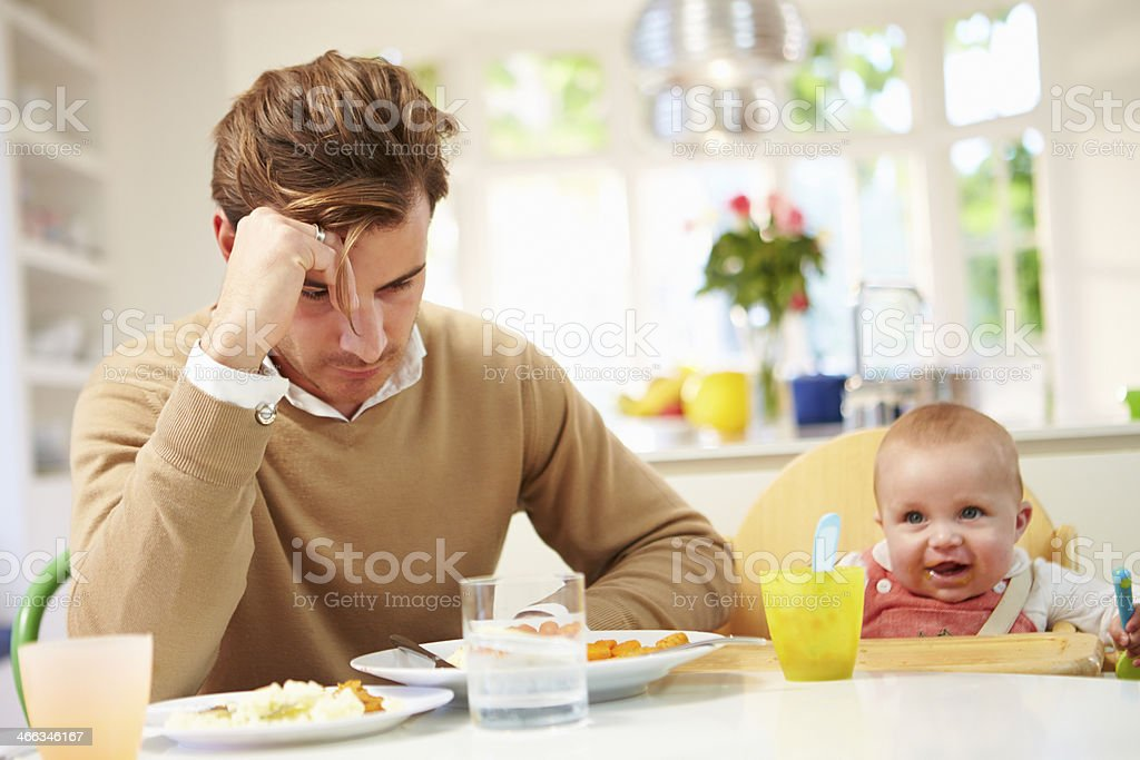 Father Feeling Depressed At Baby's Mealtime stock photo