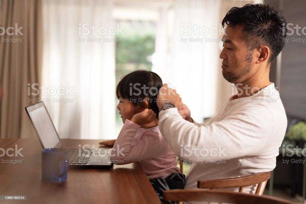 父は自宅で固定の娘の髪 ストックフォト