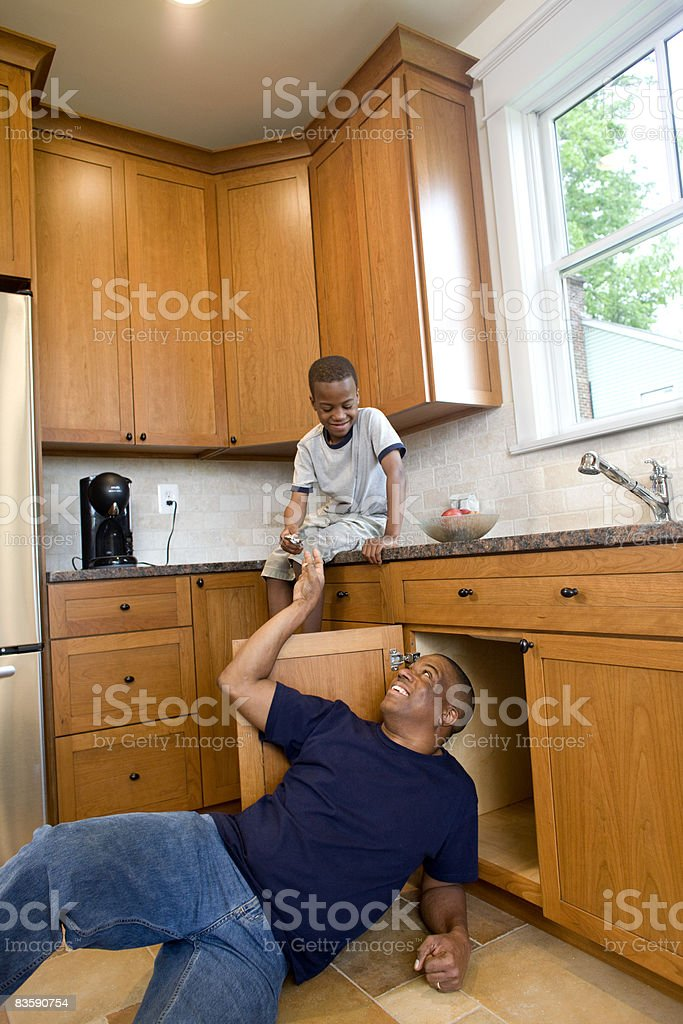Father fixing kitchen sink, son handing tools royaltyfri bildbanksbilder
