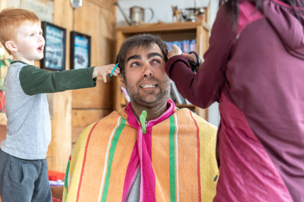 Father getting an haircut at home during stay at home order stock photo