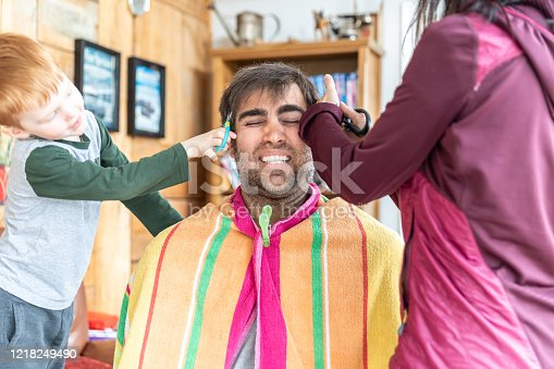 Father getting an haircut at home during stay at home order. The mother and the son are cutting hairs in the living room while the father is afraid of the final result.