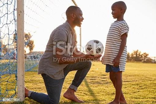 829627936istockphoto Father gives a ball to his son during a football game 829627834