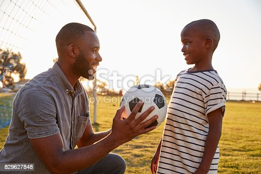 829627936istockphoto Father gives a ball to his son during a football game 829627848