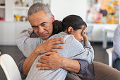 istock Father gives daughter a supportive hug in a group therapy session 1173939480
