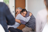 istock Father gives daughter a supportive hug in a group therapy session 1175358282