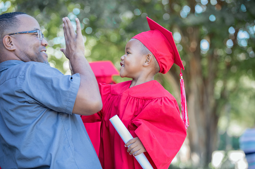 Father gives his preschool age son a high five after kindergarten graduation ceremony