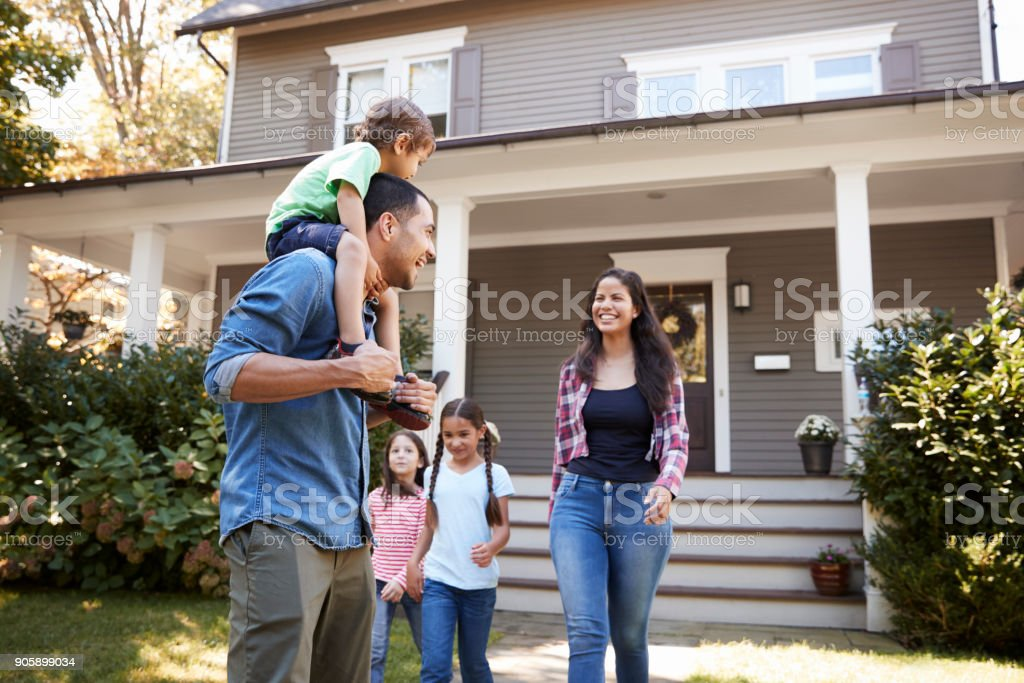 Father Gives Son Ride On Shoulders As Family Leave House stock photo