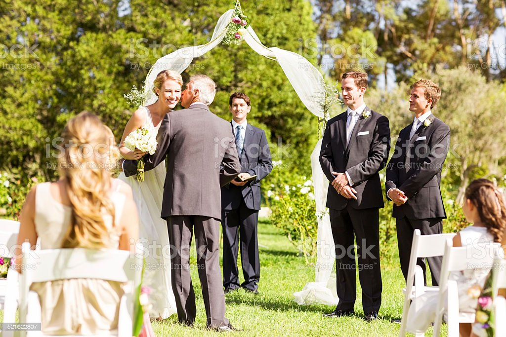 Father Giving Away The Bride At Wedding Ceremony stock photo