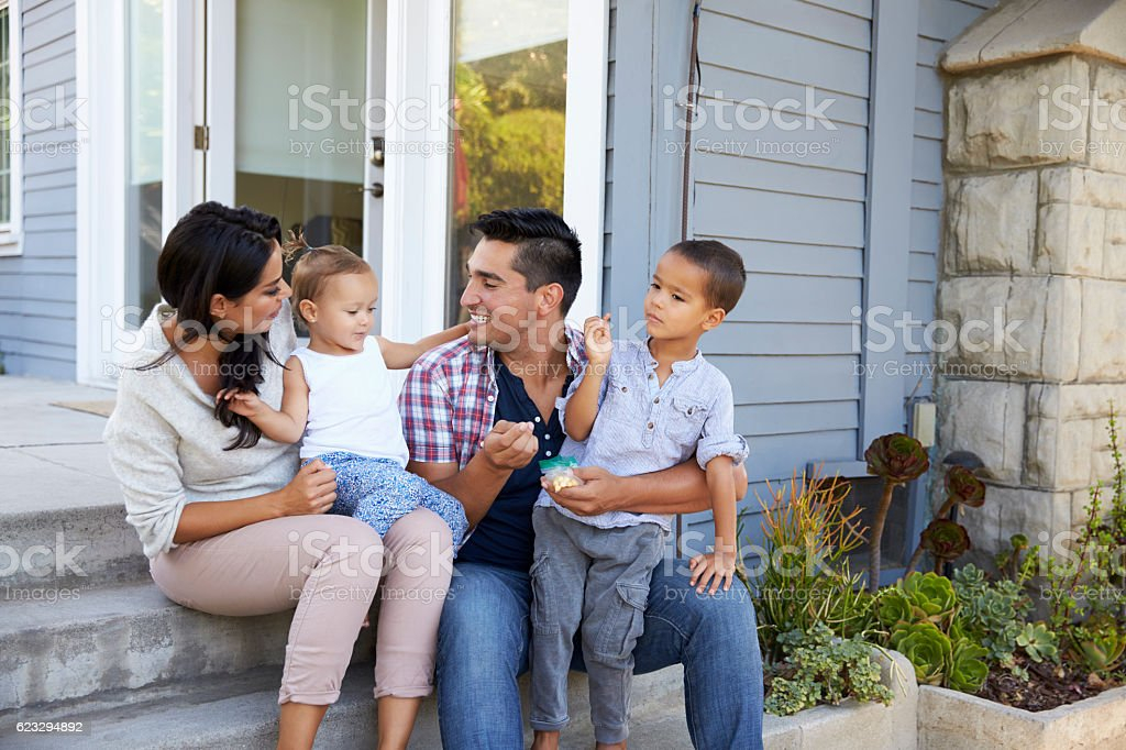 Father Giving Children Candy On Steps Outside Hose stock photo