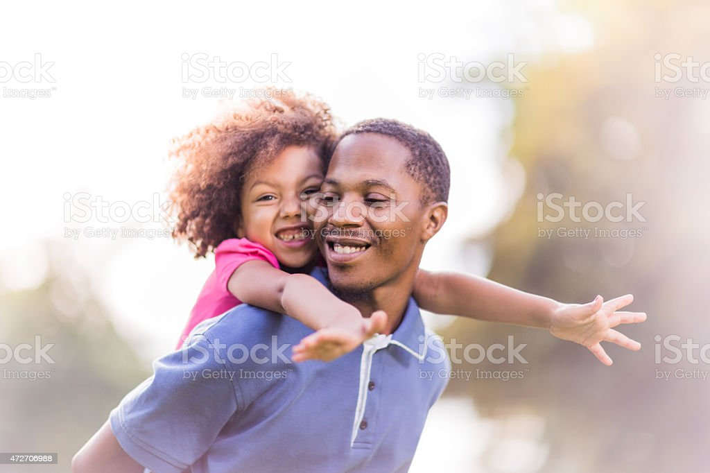 Father giving daughter a piggyback ride on a sunny day stock photo