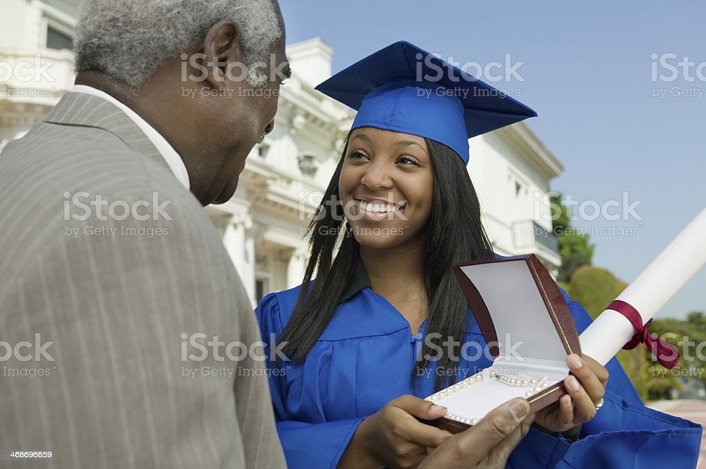 Father Giving Daughter Graduation Gift stock photo