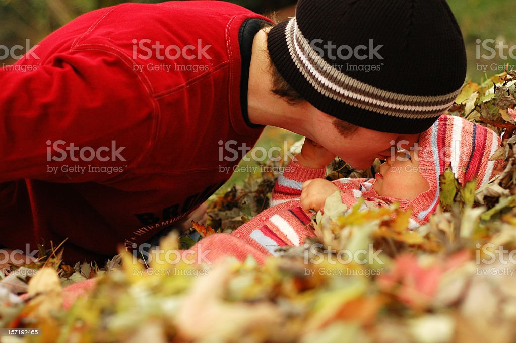 Father Giving his Daughter a Kiss in Autumn Leaves royalty-free stock photo
