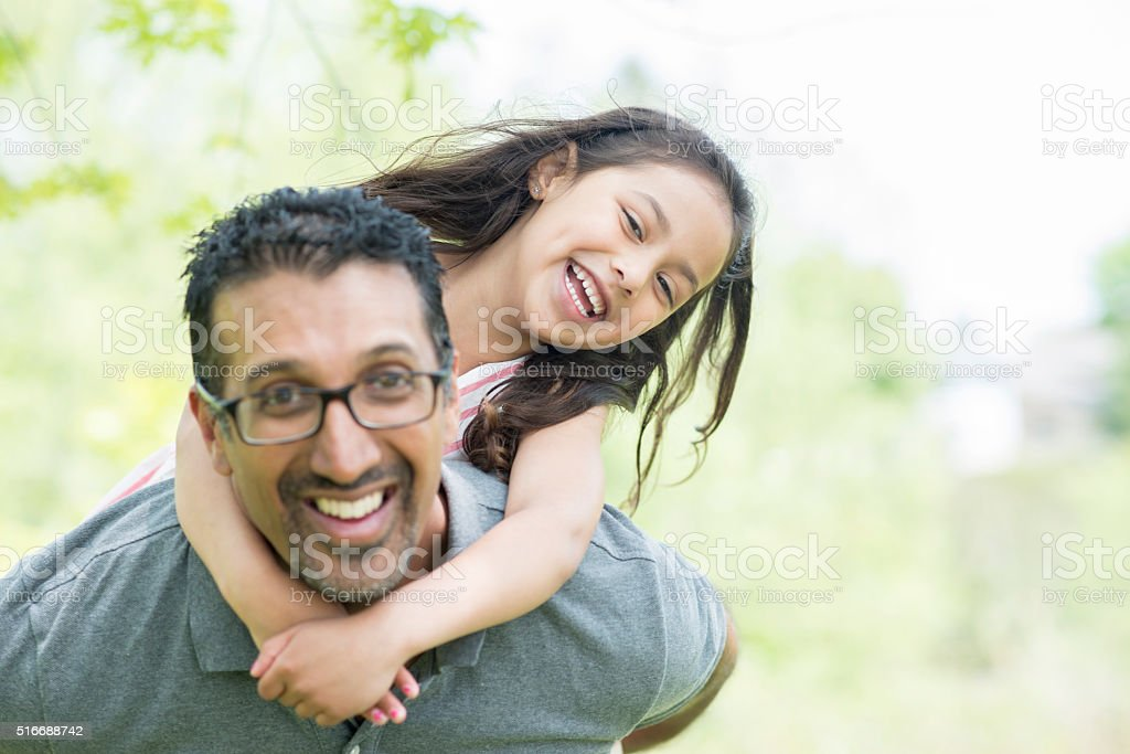 Father Giving His Daughter a Piggy Back Ride stock photo