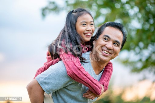 A Filipino father gives his elementary school aged daughter a piggy back ride, while they enjoy a walk outside.  They are smiling and enjoying each others company and his daughter is looking down at him.