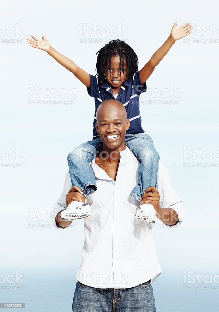 Father giving his son a ride on shoulders royalty-free stock photo