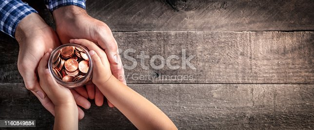 Hands Of Father Giving Jar Of Coins To Child On Wooden Table Background - Inheritance / Parent Providing For Children Concept