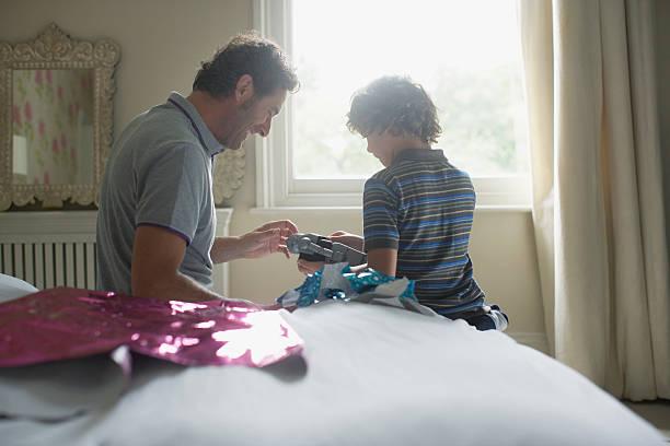 vater gibt seinem sohn ein geschenk für weihnachten - marvel schlafzimmer stock-fotos und bilder