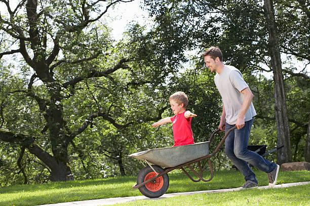 Vater gibt seinem Sohn Fahrt In Schubkarre – Foto