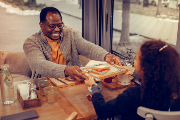 Father giving wooden plate with sandwich to his cute daughter stock photo