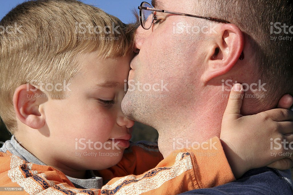 Father Giving Young Son A Kiss stock photo