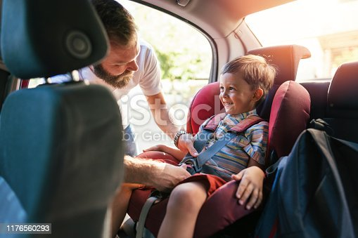 Single father getting his son buckled up with safety belts before starting their trip