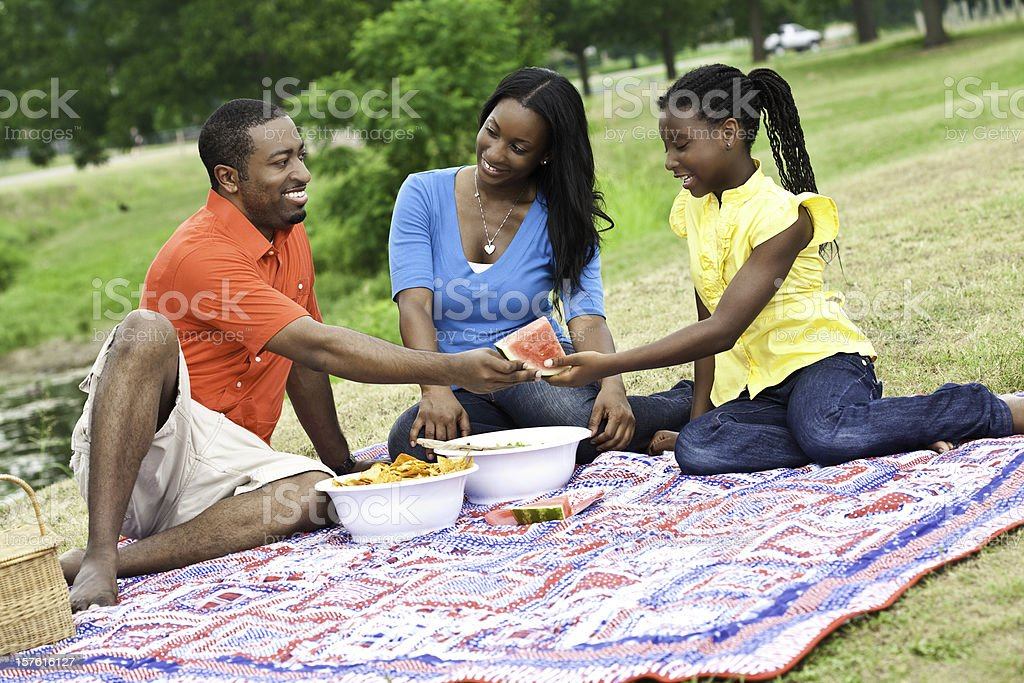 Father Handing Daughter Watermelon at Picnic In The Park stock photo