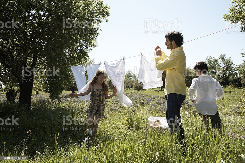 Father hanging laundry, children (8-9) running around royalty-free stock photo