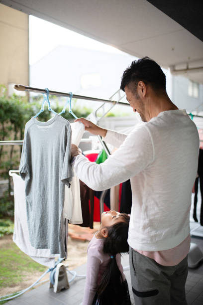 Father hanging laundry with daughter Everyday life of father and daughter at home stay at home father stock pictures, royalty-free photos & images