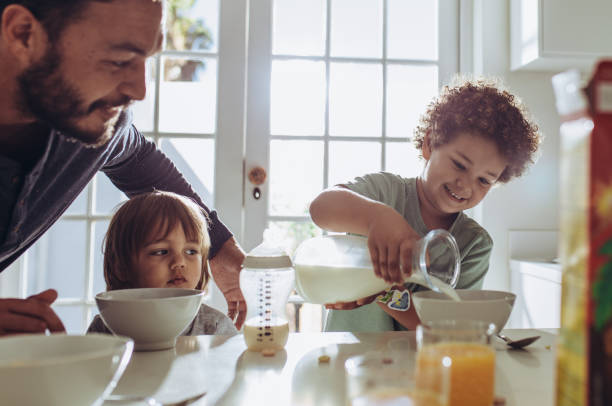 Father having breakfast with his kids at home Man watching his kid pour milk in his breakfast bowl. Father and kids sitting at the table preparing breakfast. single father stock pictures, royalty-free photos & images