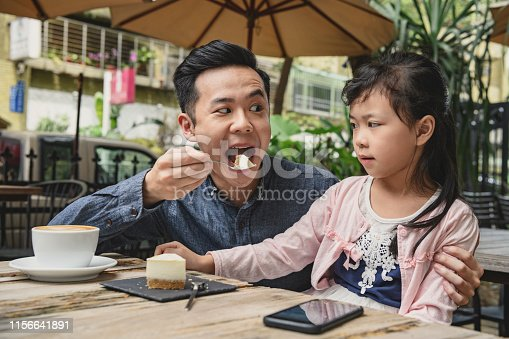 Girl looking at father with mouth wide open, eating cake outside cafe, fun, humour, young at heart