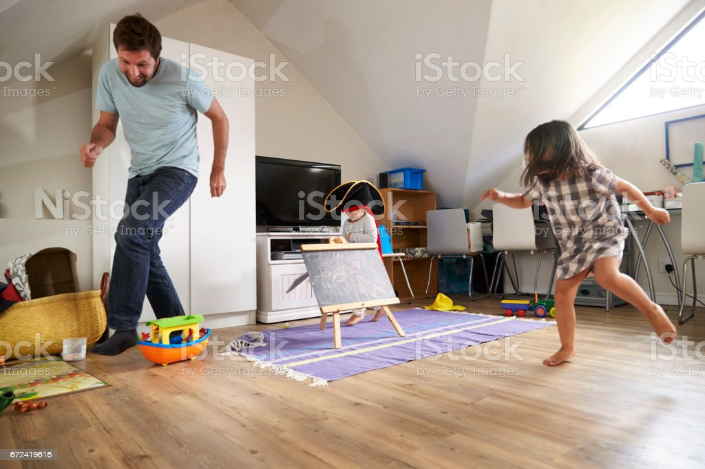 Father Having Game Of Tag With Children In Playroom stock photo