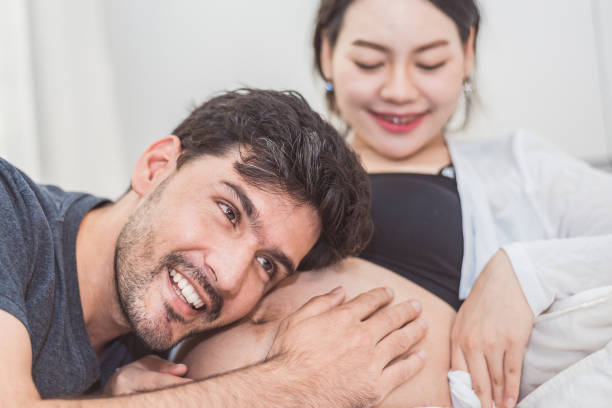father hearing his son or daughter kicking sound check inside mother belly when sitting on lying on bed at home. family healthy and couples concept. happy sweet home honeymoon and wedding theme - woman breastfeeding husband stock photos and pictures