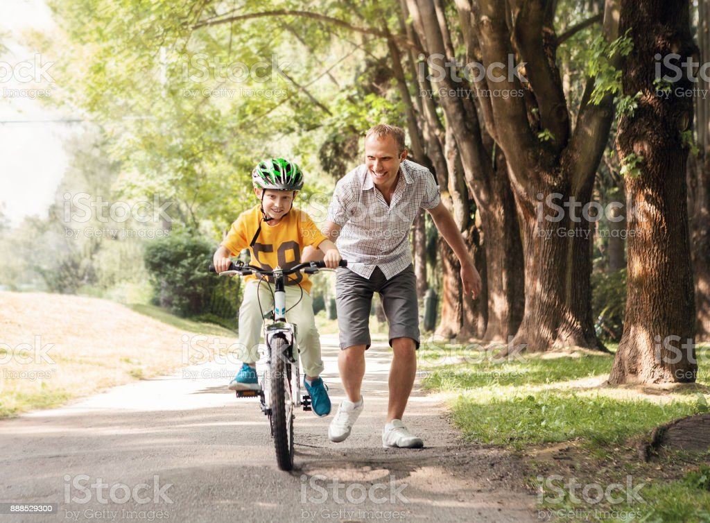 Father help his son learn to ride bicycle stock photo
