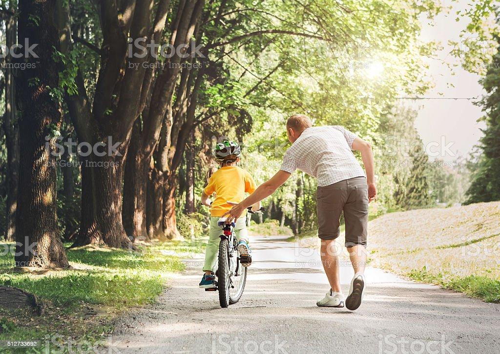 Padre ayuda un su hijo un paseo en bicicleta foto de stock libre de derechos