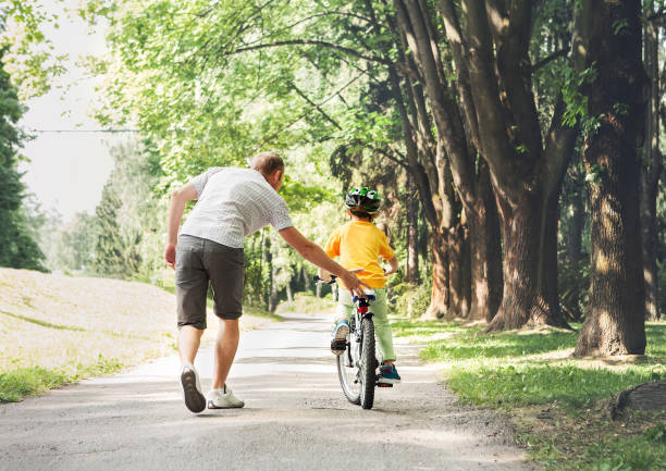 father help his son ride a bicycle - cycling stock photos and pictures