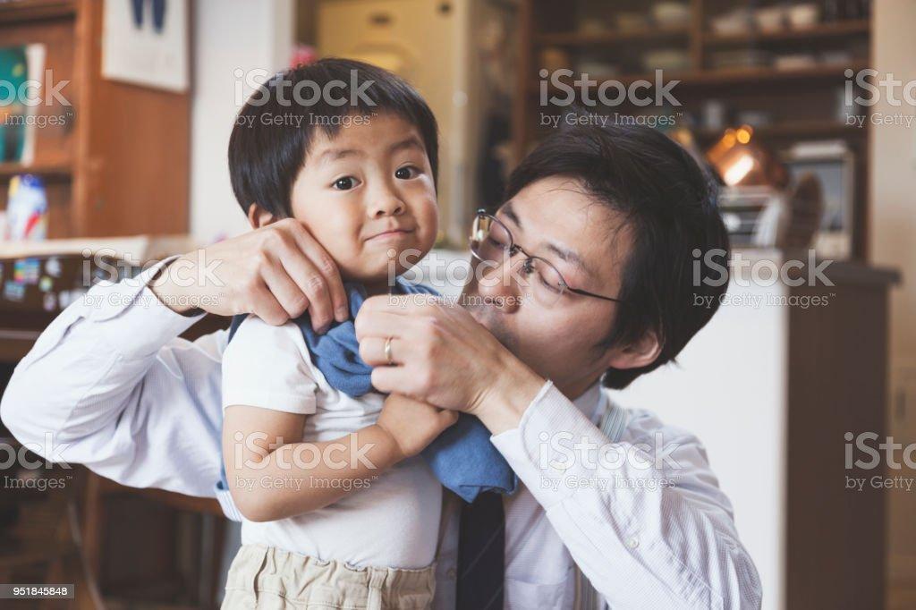 父息子の服を着るに役立つ ストックフォト