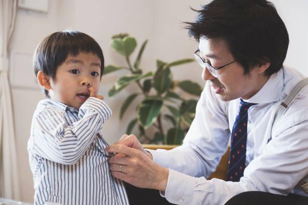 父が服を着て息子を助ける ストックフォト