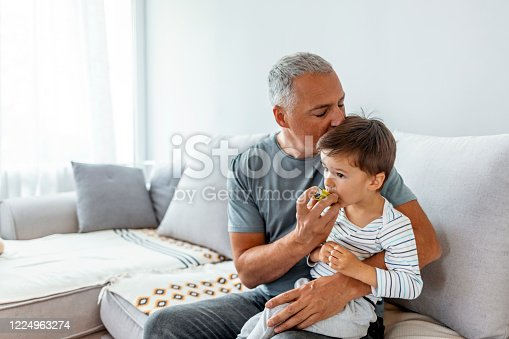 Mature father and son are sitting together in a living room. He is helping him take his puffer because he suffers from asthma.