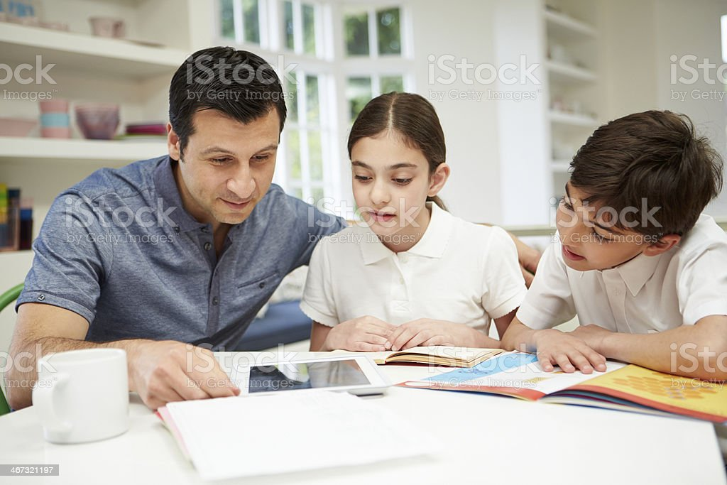 Father Helping Children With Homework Using Digital Tablet stock photo