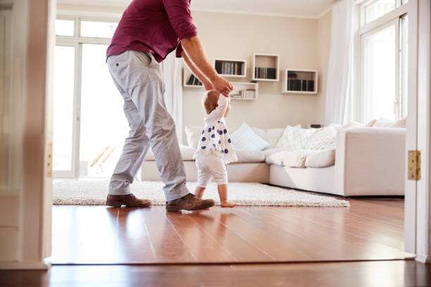 father helping daughter learn to walk at home, side view - first step stock photos and pictures