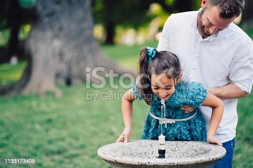 Young father and his daughter drinking water on hot summer day in the city park