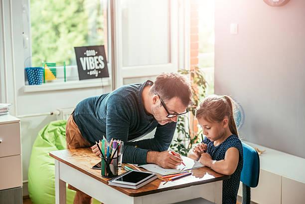 father helping daughter to finish homework - haushaltsbuch führen stock-fotos und bilder