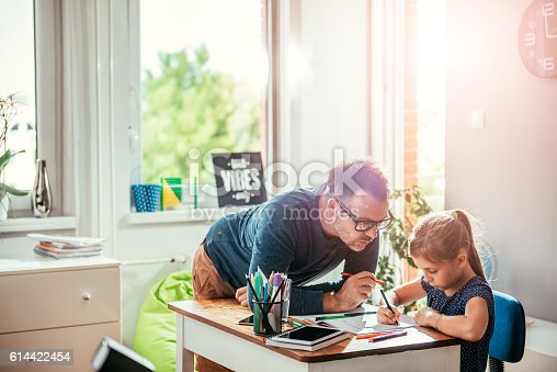 istock Father helping daughter to finish homework 614422454
