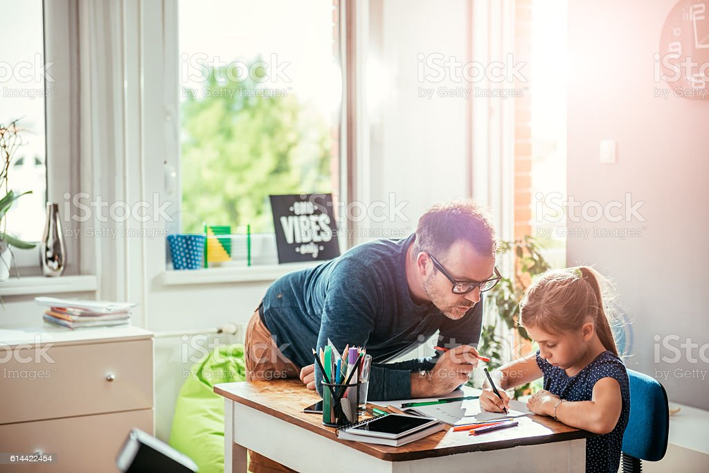 Father helping daughter to finish homework stock photo