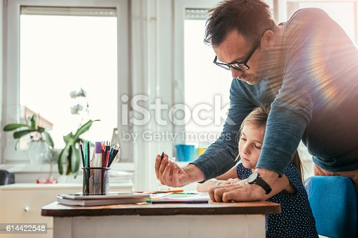 istock Father helping daughter to finish homework 614422548