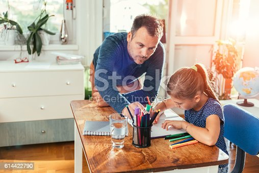 istock Father helping daughter to finish homework 614422790
