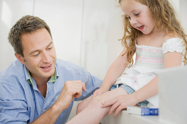 father helping daughter with bandage - open wounds stock photos and pictures