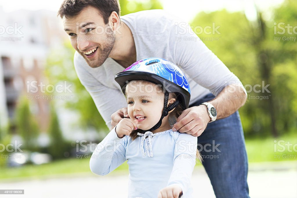 Father helping daughter with bike helmet stock photo